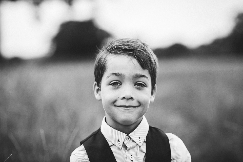 little boy in field black and white