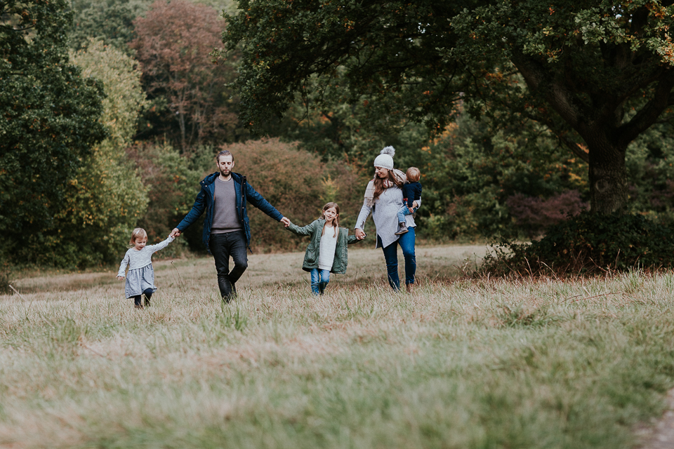 family holding hands a walking in the field for outdoor phtoto session
