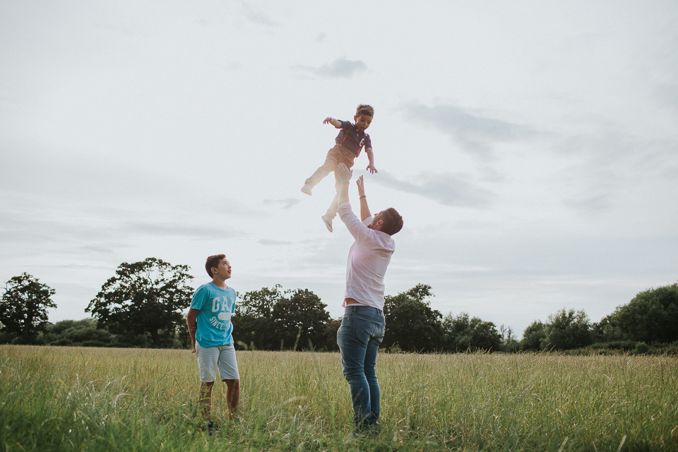 Dad throwing child in the air during families outdoor photoshoot