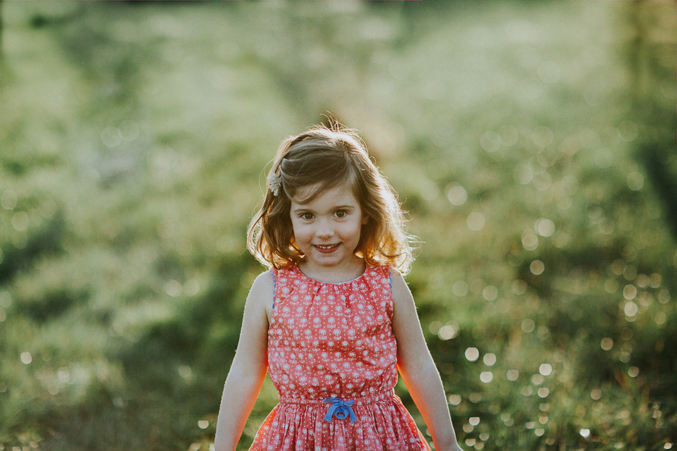 little girl smiling in sunset on families portrait session