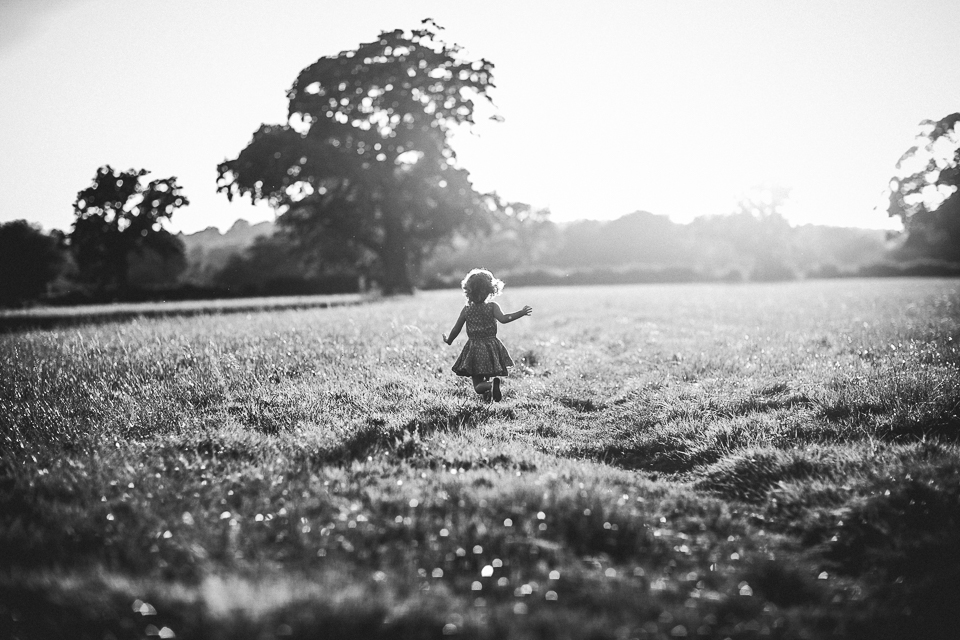 little girl running into sunset black and white family session