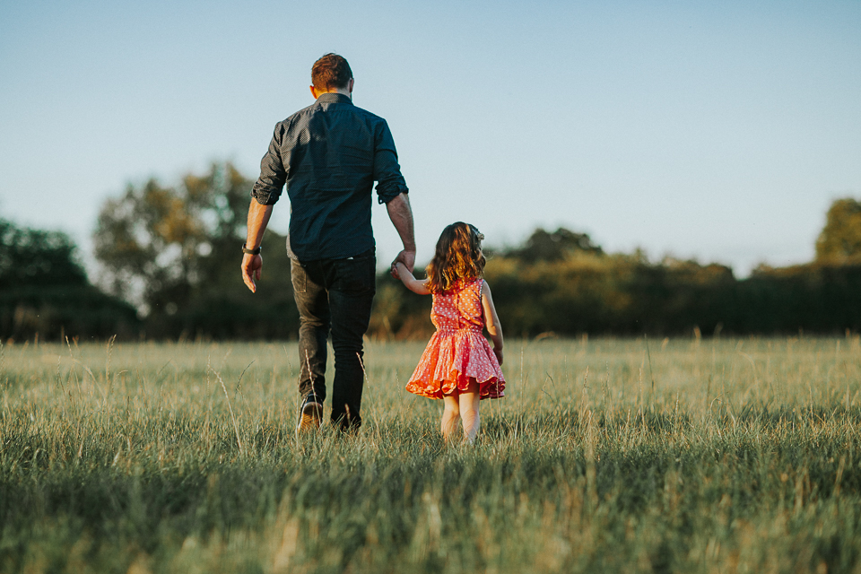 little girl holding daddy hand walking in sunset