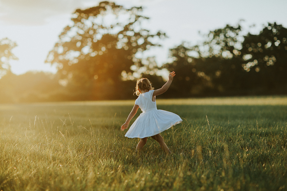 little girl twirling in the sunset