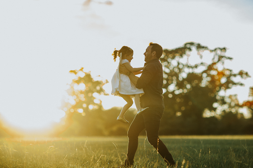 dad running with little girl at sunset