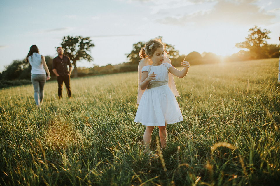 little girl with angel wings in a field with parents