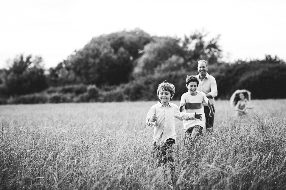 family running in the long grass outdoor family photoshoot