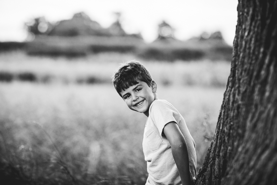 little boy by a tree black and white portrait