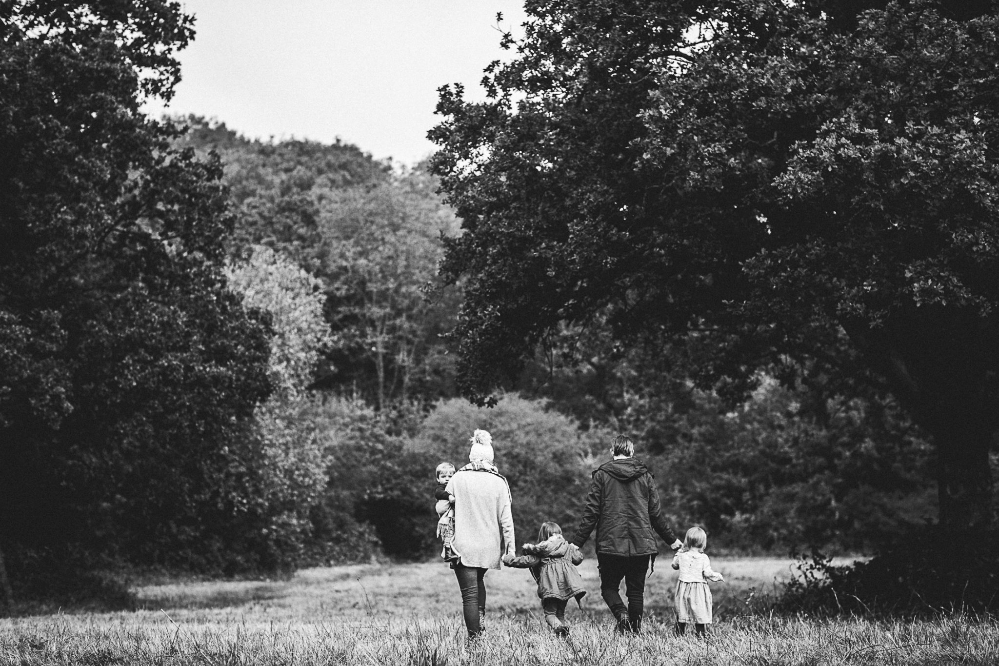 family holding hands walking away into a field