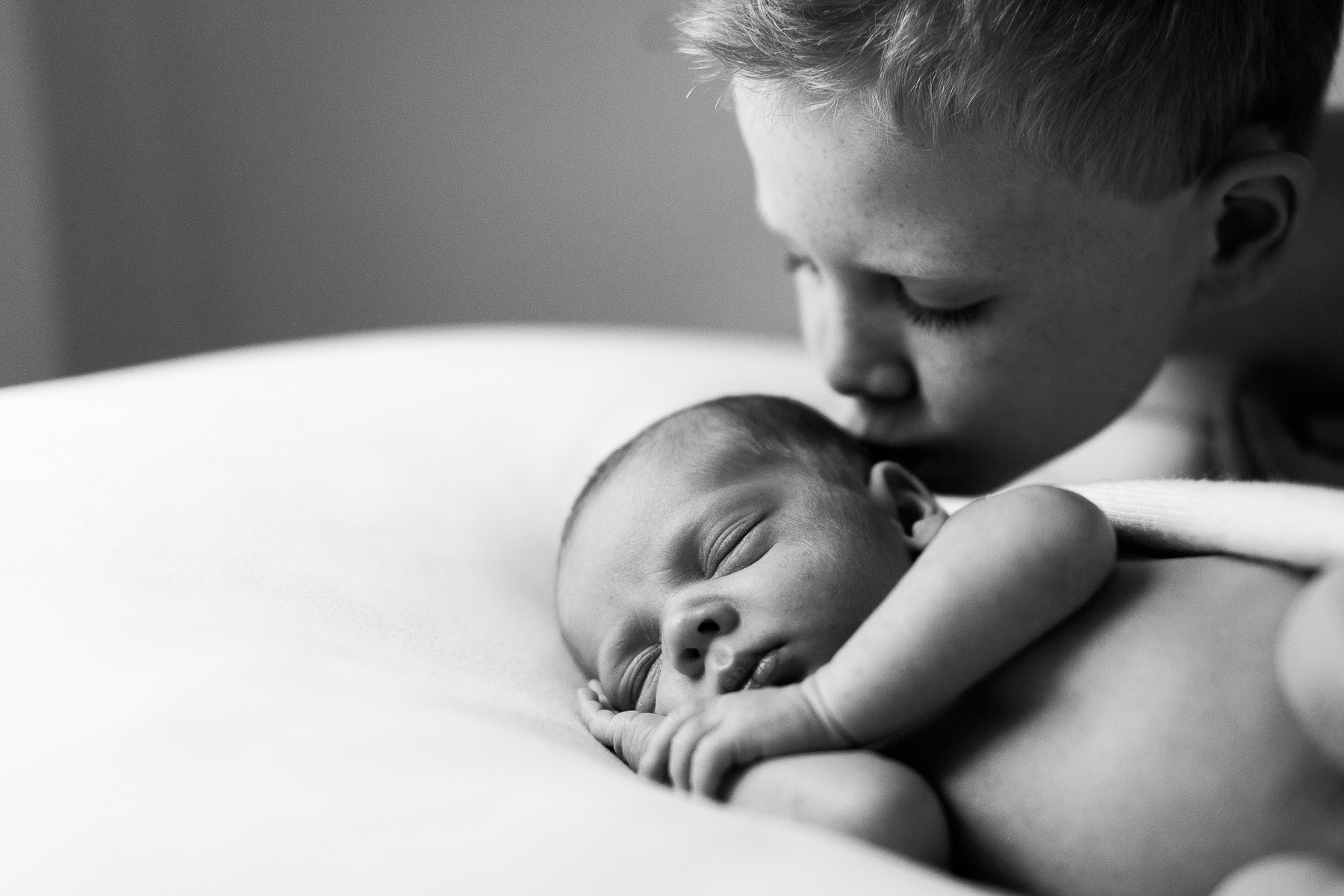 boy kissing newborn baby brother